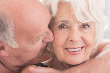 erotic: Cropped picture of a senior woman smiling at the camera and her husband kissing her on the cheek Stock Photo