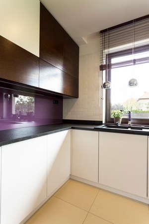 cupboards: Light kitchen idea with white and black cupboards, dark worktop and violet backsplash
