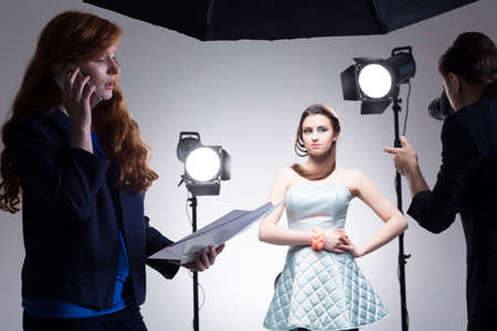 fashion shoot: Shot of a young woman talking on a phone during a fashion photoshoot Stock Photo
