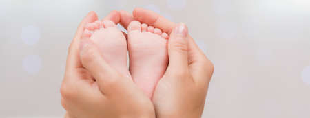 Close-up of tiny newborn's feet in the hands of a mother