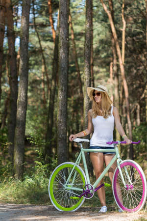 sun hat: Young woman with sun glasses and sun hat standing with her modern bike in the forest