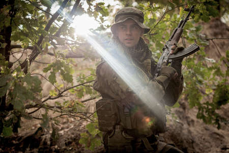 proving: Shot of a soldier with weapon in his hands, standing in the middle of the trees and bushes Stock Photo