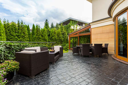green building: Shot of a spacious terrace with black furniture surrounded by a garden