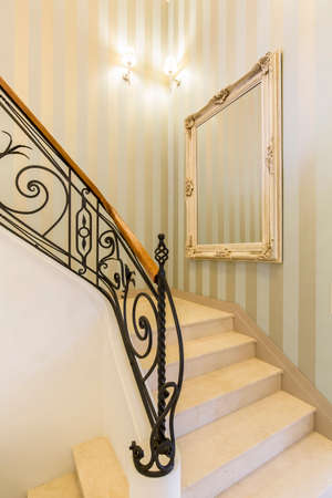 elegant staircase: Marbled stairway with decorative metal railing in a luxurious interior