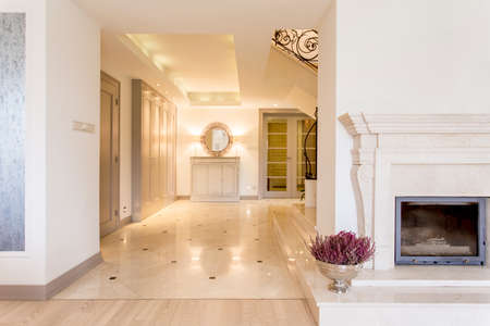moulded: Grand marble anteroom in a contemporary villa bordering a living room with moulded fireplace