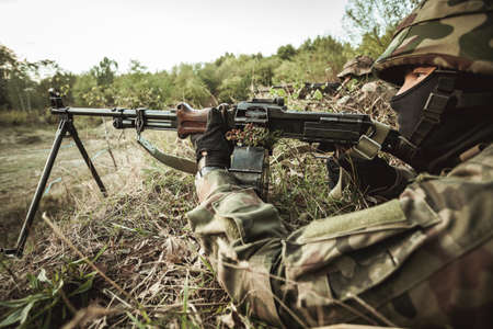 proving: Soldiers laying on a training ground in camo and pointing a gun Stock Photo