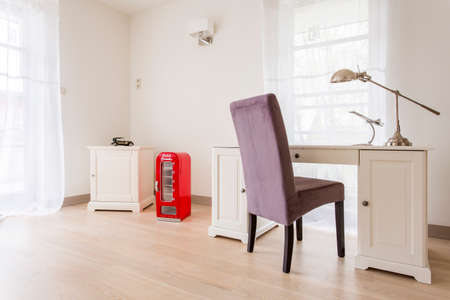 Cette chambre lumineuse et aérée avec un bureau classique blanc et le tiroir, et une violette rembourrés chaise Banque d'images - 61115092