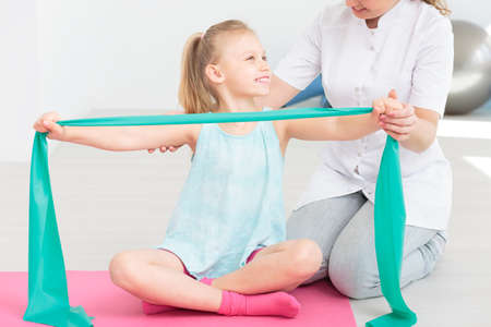 stretching condition: Smiling little girl sitting on mat and stretching rubber band