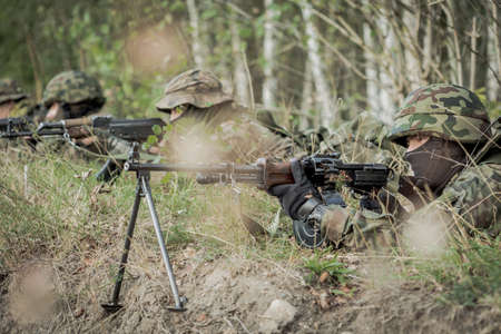 proving: Soldiers laying on a training ground with the weapon with the forest behind them