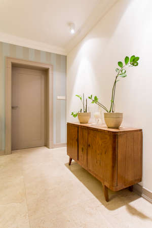 stone floor: Cosy and stylish hall with marble floor and a renovated vintage dresser