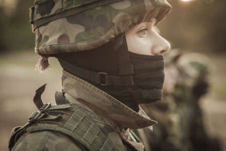 proving: Close shot of young soldier face in camo helmet with other soldiers at the background