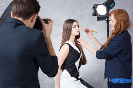 Disparo de un fotógrafo toma una foto de una modelo joven y un especialista en maquillaje