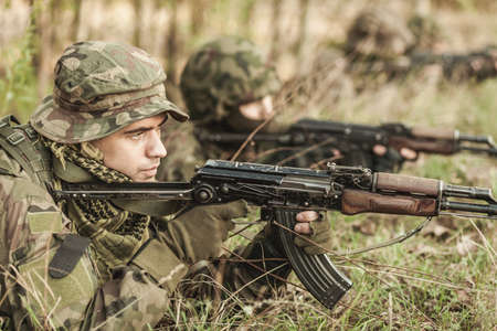 proving: Shot od soldiers laying on a training ground in camo and pointing a gun to the objects Stock Photo