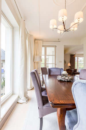 upholstered: Fragment of a dining room in a very luxurious house, with wooden table and upholstered chairs Stock Photo