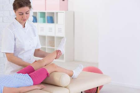 patiënt kind tijdens fysiotherapie met professionele jonge fysiotherapeut Stockfoto