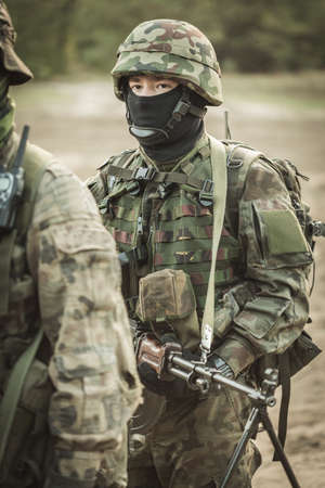 proving: Shot of a soldier in camouflage clothes and helmet with a weapon in his hands