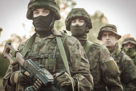 proving: Shot od soldiers with weapon standing in camo and helmets single file on a training ground Stock Photo