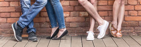 red brick: Close-up of young people legs on red brick wall Stock Photo