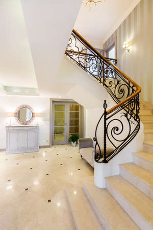 banister: Very spacious hall and staircase of a mansion, with marble floor and steps, decorative metal banister and a vanity