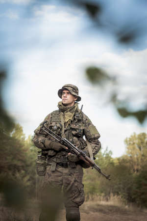 proving: Shot of soldier in camo and weapon in his hands, standind alone on a training ground Stock Photo