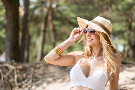 easygoing: Close shot of a young woman with sun glasses and sun hat in summertime with the forest behind her Stock Photo