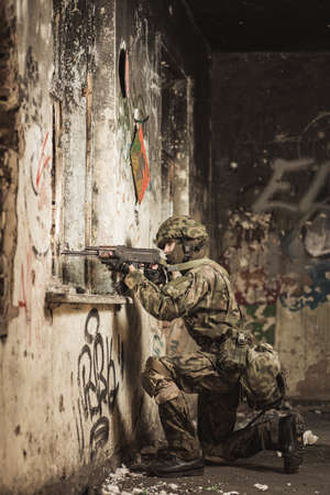 proving: Camouflaged soldier in helmet kneeling close to the hole in the wall with a weapon in an ruined and scruffy walls Stock Photo