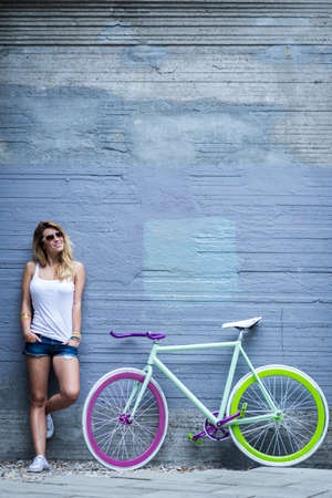 easygoing: Young woman standing close to her modern bike with the concrete wall behind her