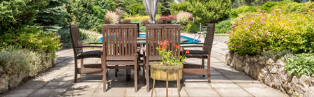 apartment building: Shot of a wooden garden furniture set surrounded by greenery Stock Photo