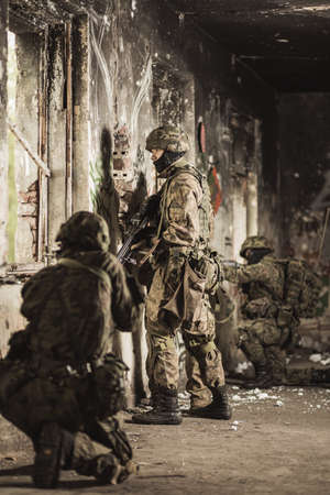proving: Soldiers in camouflage clothes and helmets standing and kneeling close to the wall in a scruffy and ruined walls