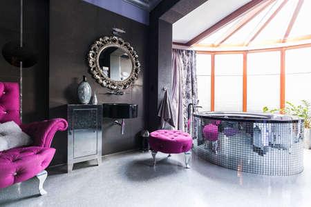 black bathroom: Shot of a stylish black bathroom with violet furniture and a big bathtub