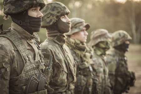 proving: Five soldiers standing in a rank in camouflage clothes and helmets