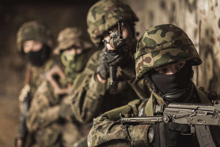 proving: Four soldiers standing single file close to the wall in helmets and with the weapon