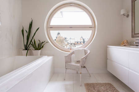 round: Elegant bathroom with bright tiles and a rattan chair beside a large round window overlooking the neighbourhood