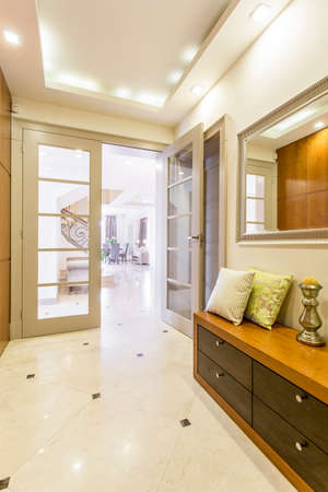 anteroom: Elegant and stylish anteroom of a modern villa, with marble floor, chest of drawers and large door Stock Photo
