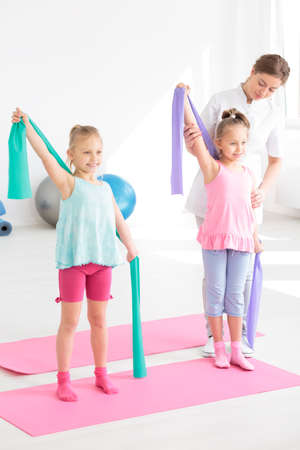 Little girls exercising with elastic band during physiotherapy