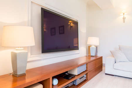 tv set: Bright and spacious living room with a tv set and a long hi fi cabinet with two lamps standing on it
