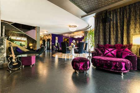 Colpo di un ampio soggiorno con mobili rosa e un pavimento nero