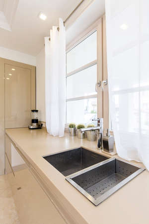 double sink: Chrome kitchen sink with drainer next to a large window in a luxurious kitchen Stock Photo