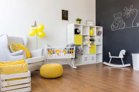 hassock: Unisex space- cosy baby room and yellow decorations Stock Photo