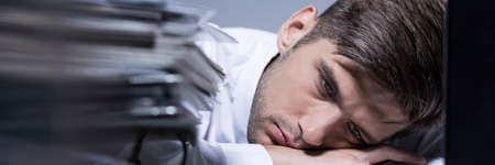 company job: Exhausted overworked businessman lying with his head on desk at his office, panorama Stock Photo