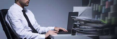agotado: Business worker working late at night on his laptop, sitting beside desk, panorama