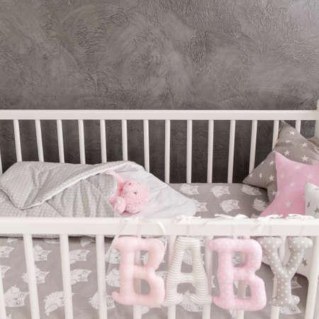baby crib: Shot of a baby crib in a grey nursery