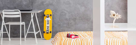 bedcover: Orange skateboard by a grey stucco wall and a comfortable bed