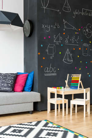small table: Shot of a modern kids room interior with a large blackboard and small table with chairs Stock Photo