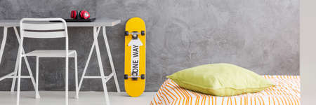 bedroom wall: Orange skateboard leaning on a grey stucco wall of modern bedroom