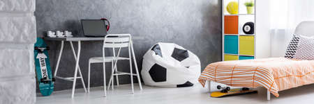 bedcover: Skateboarders room with football sit sack and longboard under the bed Stock Photo