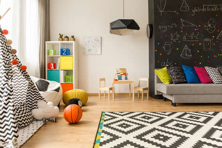 Shot of a kids room with a grey sofa, large blackboard and a place for learn