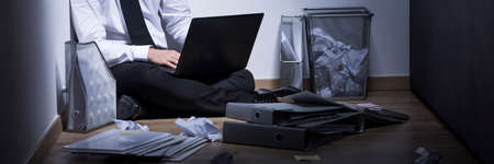 work addicted: Businessman addicted to work sitting on a floor with laptop among documents, panorama
