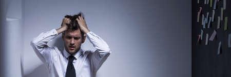 cansancio: Deprimido hombre de negocios sentado en un piso de manos sobre la cabeza, panorama