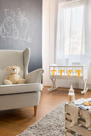 natural light: Teddy bear on armchair in bright infant baby room Stock Photo